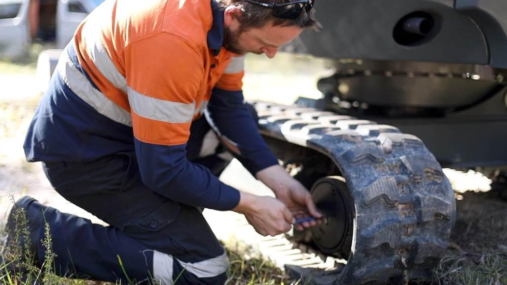 man is fixing the wheel of the excavator